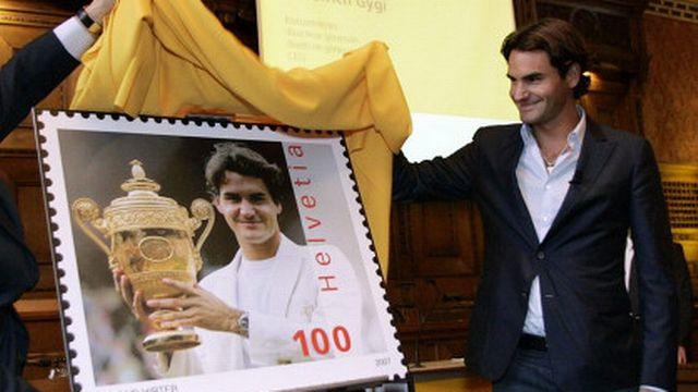 Roger Federer tout sourire à côté du timbre à son effigie [Keystone]