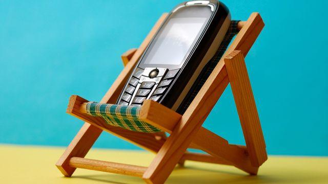 Utiliser son téléphone portable durant les vacances à l'étranger peut coûter cher. Natel, chaise longue, vacances [miqul - Fotolia]
