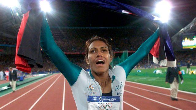 Sydney 2000: l'Australienne Cathy Freeman effectue un tour d'honneur après sa victoire sur le 400 m des jeux Olympiques en brandissant deux drapeaux. Le drapeau australien et le drapeau aborigène, pour rappeler ses origines et tenter de réconcilier les descendants des européens et des aborigènes. [PB/JDP - Reuters]