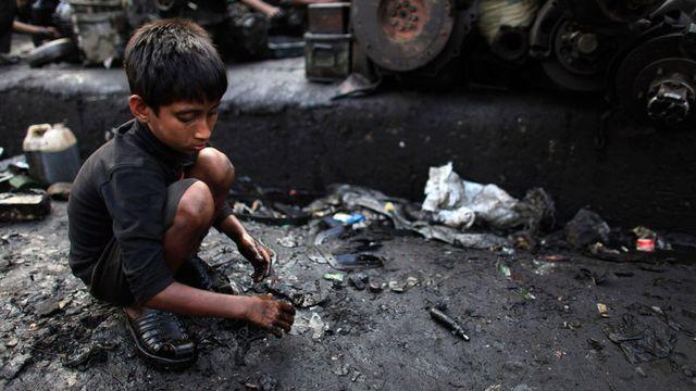 Masud, six ans, récolte de la ferraille dans le quartier de Dholaikal, à Dhaka, Bangladesh.  [Andrew Biraj - Reuters ]