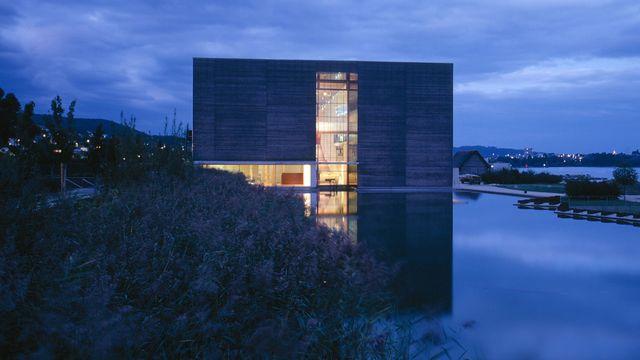 Le Laténium au crépuscule, depuis l'étang piscicole du parc du musée. [Yves André - Laténium Neuchâtel]