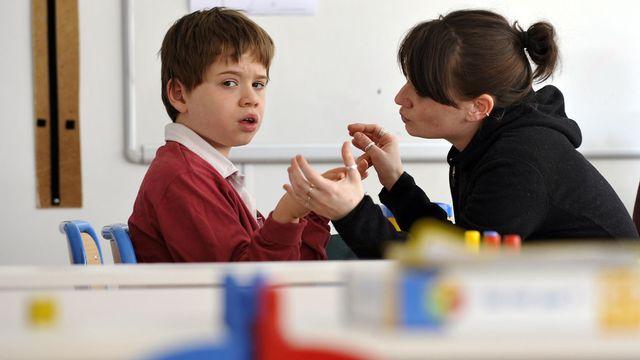 Un enfant autiste travaille avec une éducatrice. [Franck Fife - AFP]