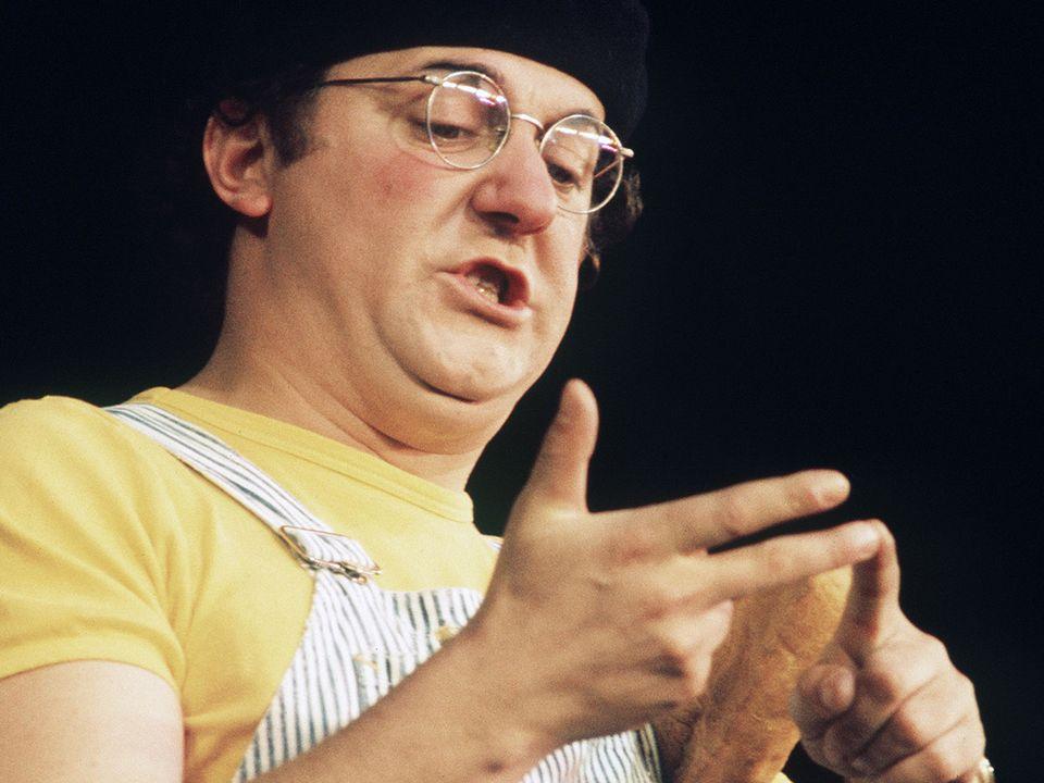 Le chansonnier-fantaisiste Coluche, vêtu de sa traditionnelle salopette rayée sur la scène de l'Olympia en 1975. [AFP]