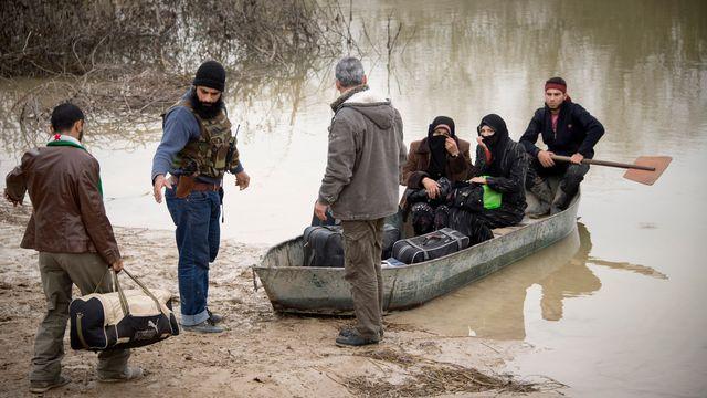 Des rebelles aident deux femmes syriennes à fuir vers la Turquie. [AFP]