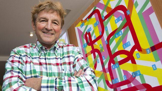 Daniel Rossellat, président du festival, pose devant l'affiche de la 37e édition du Paléo. [Keystone]
