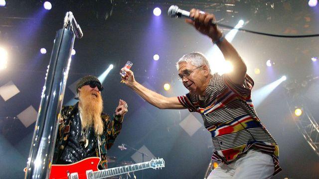 Claude Nobs se lâche sur la scène du Montreux Jazz Festival sous les yeux de Billy F. Gibbons, le chanteur des ZZ Top (juillet 2003). [Fabrice Coffrini - Keystone]