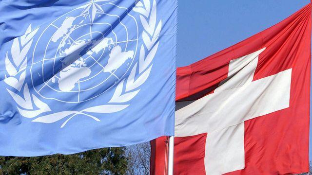 Le logo de l'ONU - blanc sur fond bleu - est une carte du monde entourée de rameaux d'olivier, symboles de paix. Par souci d'équité, la représentation du monde est équidistante et azimutale, centrée sur le pôle nord.  [Laurent Gillieron - Keystone]