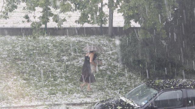 Une passante tente de s'abriter de la grêle jeudi vers 16h sur l'Avenue Giuseppe-Motta, face au Parc Trembley, à Genève. [Noël Lugnon - vosinfos]