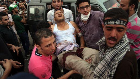Des partisans de Mohamed Morsi portent un homme blessé dans les heurts avec l'armée. [AP Photo/Khalil Hamra - Keystone]