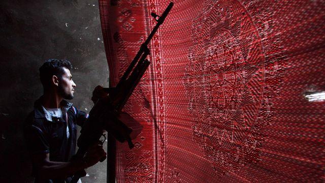 Un combattant de l'armée syrienne libre se cache derrière un tapis dans la province de Daïr az Zour dans l'est de la Syrie le 25 juillet 2013. [Khalil Ashawi - Reuters]