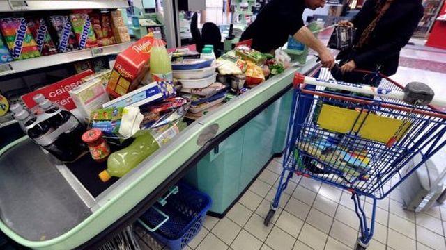 Une personne passe en caisse, dans un supermarché [AFP]