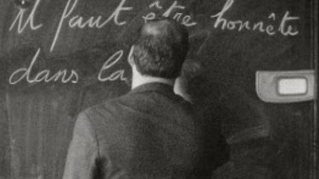 Leçon d'écriture au tableau noir par l'instituteur. [RTS]