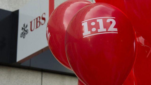 Des ballons aux couleurs de l'initiative 1:12 sont accrochés devant le logo de la banque UBS lors du lancement de la campagne sur l'initiative 1:12 dans les cantons romands ce jeudi 17 octobre 2013 devant le siege UBS à Sion.  [Jean-Christophe Bott - Keystone]