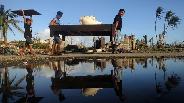 Les Philippins essayent de récupérer du matériel et de la nourriture.  [Noël Celis - AFP]