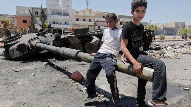Enfants syriens jouant avec les restes d'un tank, Alep le 3 août 2012. [Ahmad Gharabli - AFP]