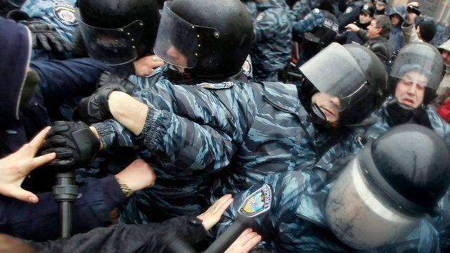 Lundi 25 novembre: les forces de l'ordre ukrainiennes tentent de contenir les manifestants qui cherchent à s'approcher des bâtiments ministériels à Kiev. [EPA/Sergey Dolzhenko - Keystone]