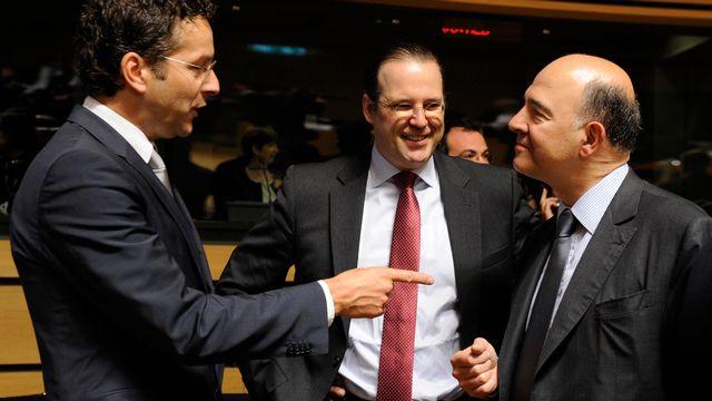 Le ministre des Finances français Pierre Moscovici (d.) en conversation avec ses homologues néerlandais, le président de l'Eurogroupe Jeroen Dijsselbloem (g.), et suédois, Anders Borg (c.). [John Thys - AFP]