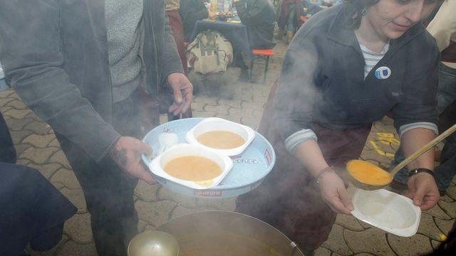 Des bénévoles préparent les assiettes de soupe pour les personnes défavorisées. [Salvatore Di Nolfi - Keystone]