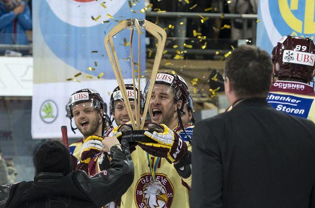 Le capitaine de Genève-Servette Goran Bezina soulève le trophée de la Coupe Spengler. [Peter Schneider - Keystone]