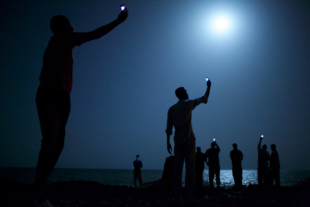 La photo de l'année du World Press Photo 2014 a été prise par l'Américain John Stanmeyer pour le National Geographic. Des migrants africains, rassemblés sur les côtes de Djibouti, cherchent à capter le réseau mobile de la Somalie voisine.