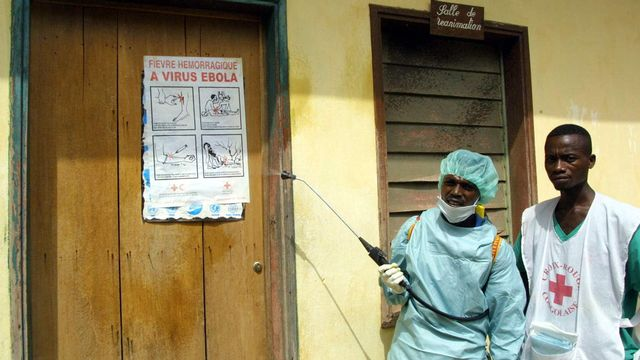 Des travailleurs de la Croix-Rouge désinfectant une salle de soins intensifs. [Desirey Minkoh - AFP]
