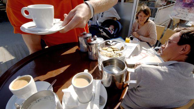 Un serveur, travailleur saisonnier apporte des café à des clients. Image d'archives. [Mychele Daniau - AFP]