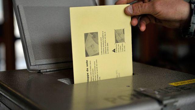 Une personne dépose son bulletin de vote dans une urne, en ville de Lausanne, ce dimanche 13 mars 2011, lors des élections communales. [Dominic Favre - Keystone]