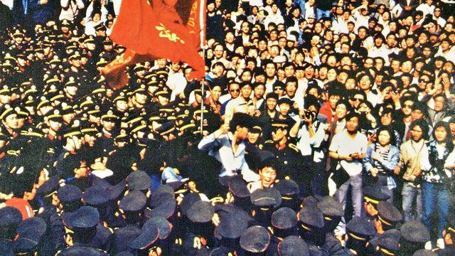 """Les étudiants portent Wu'er Kaixi, qui tient le drapeau de son école, contre un """"mur de policiers"""". [www.64museum.org]"""