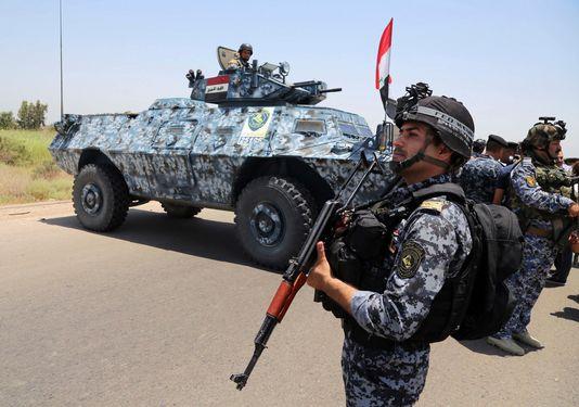 Des policiers irakiens patrouillent dans la banlieue de Bagdad. Pour faire face aux djihadistes de l'EIIL, qui s'emparent de larges territoires du pays, le pays reçoit l'aide de l'Iran et des avions russes. [Keystone]