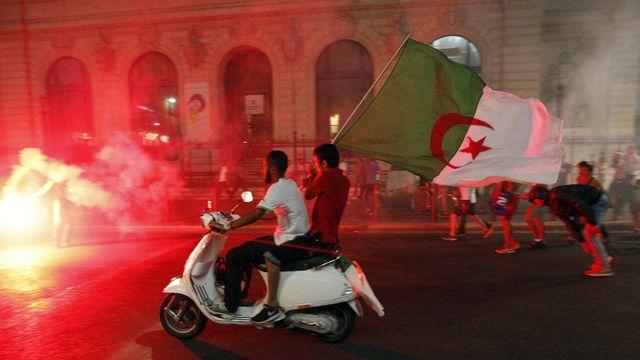 Des supporters algériens fêtent la qualification de leur équipe nationale pour les huitièmes de finale de la Coupe du monde à Marseille. [AP Photo/Claude Paris - Keystone]