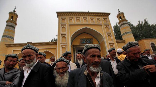 Des Ouïghoures devant la mosquée où a été tué l'imam. [EPA/HOW HWEE YOUNG - Keystone]