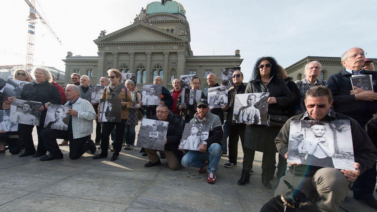 D'anciens enfants placés de force posent avec des photos d'eux, à l'époque, devant le Palais fédéral à Berne en mars 2014. [Lukas Lehmann - Keystone]