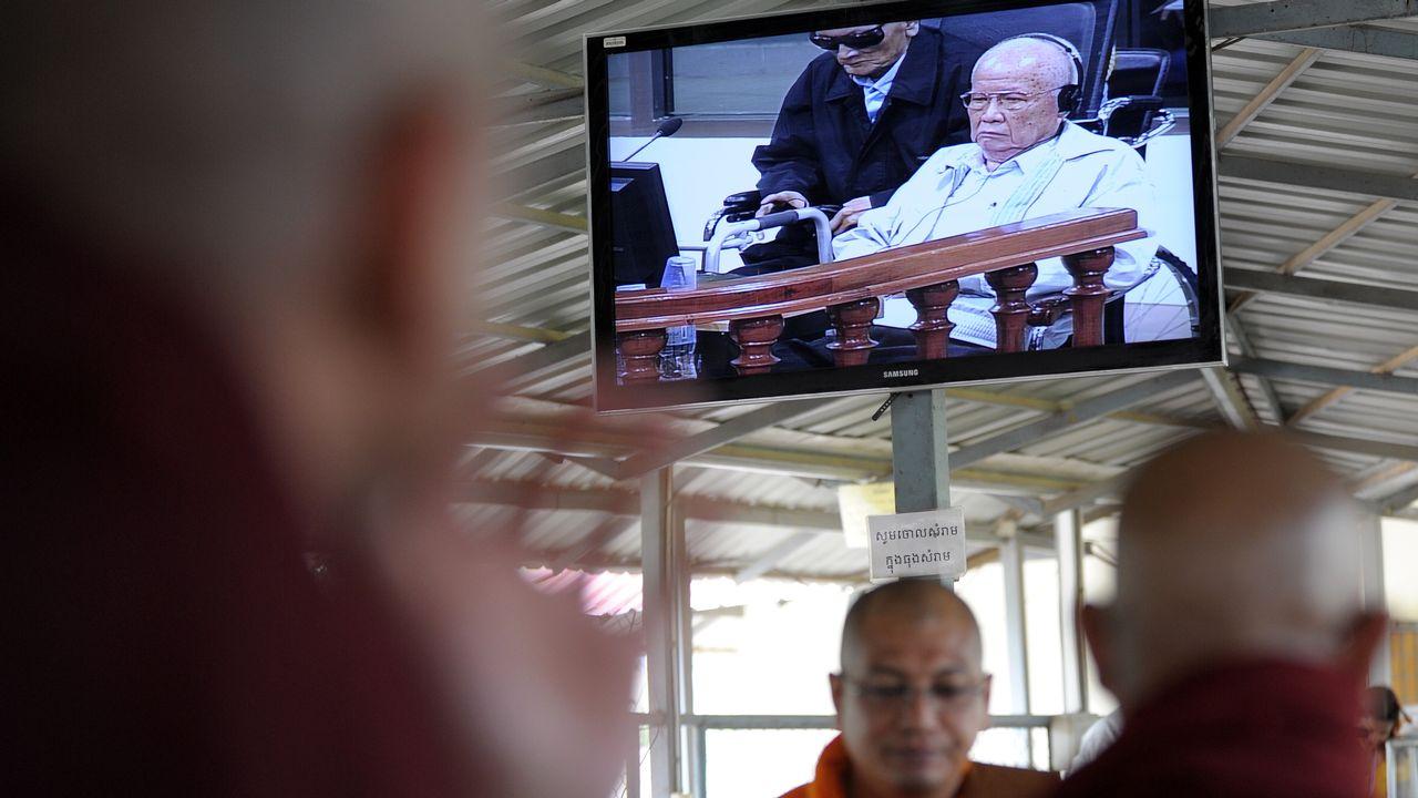 Des moines bouddhistes ont suivi jeudi le procès des ex-leaders khmers rouges Nuon Chea (à gauche) et de Khieu Samphan (à droite) à l'écran en Birmanie. [TANG CHHIN SOTHY AFP - AFP]