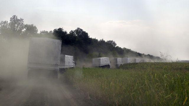 Les premiers camions d'aide humanitaire russe sont déjà de retour en Russie. [Sergei Grits - AP Photo/Keystone]