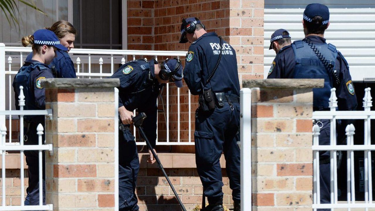 Des policiers passent une maison au détecteur de métaux, ce jeudi 18 septembre à Sydney. [DEean Lewins - Keystone]