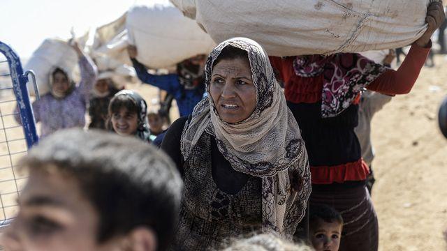Des Kurdes syriens franchissent la frontière turque à Suruc, ce mardi 23 septembre. [AFP]