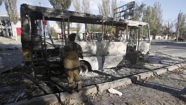 Un rebelle pro-russe examine un bus détruit après un bombardement, le 1er octobre, dans la ville de Donetsk. [Darko Vojinovic - Keystone]