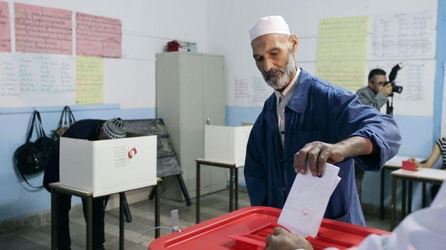 Un homme glisse son bulletin dans l'urne à Tunis, le 26 octobre 2014. [Anis Mili  - Reuters]
