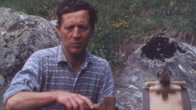 Paysan utilisant une baratte à beurre en Valais en 1976. [RTS]