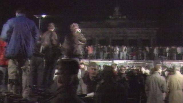 Foule de Berlinois sur le mur de la honte pour célébrer sa chute dans la nuit du 9 novembre 1989. [RTS]