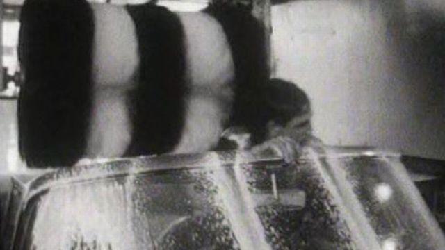 Un client se laisse prendre dans une station de lavage de voitures à Genève en 1963. [RTS]