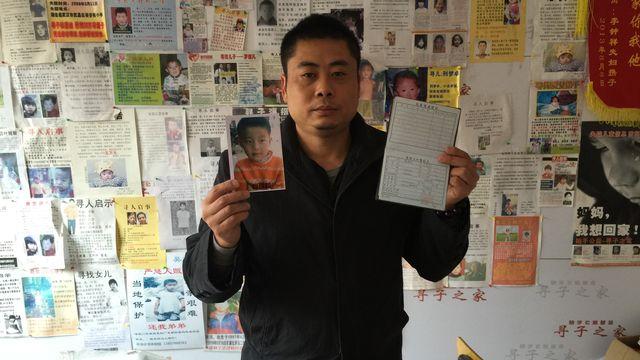 Xiao Chaohua tenant dans ses mains les papiers d'identité de son fils enlevé en 2005. [DONG Cao - RTS]