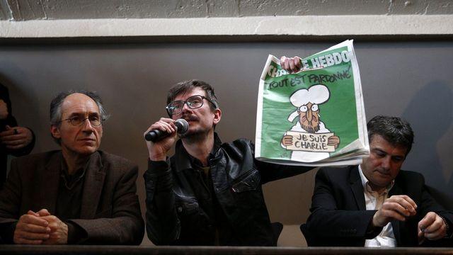 """Le dessinateur Luz, qui a signé la Une, présente le dernier numéro de Charlie """"Hebdo"""". [EPA/YOAN VALAT - Keystone]"""