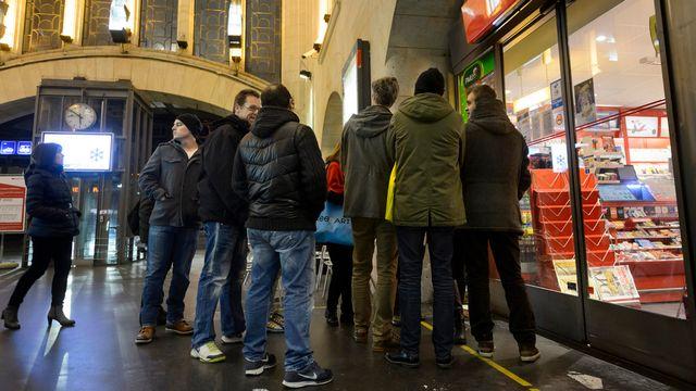Des clients attendaient impatiemment l'ouverture d'un kiosque à la gare de Lausanne jeudi pour acheter leur copie de Charlie Hebdo. [Laurent Gillieron - Keystone]