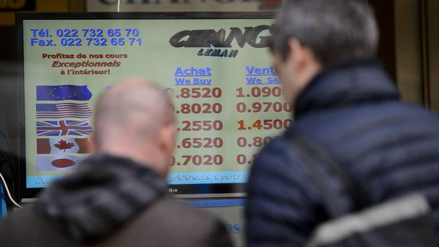 Des personnes devant un bureau de change jeudi à Genève. [Martial Trezzini - Keystone]
