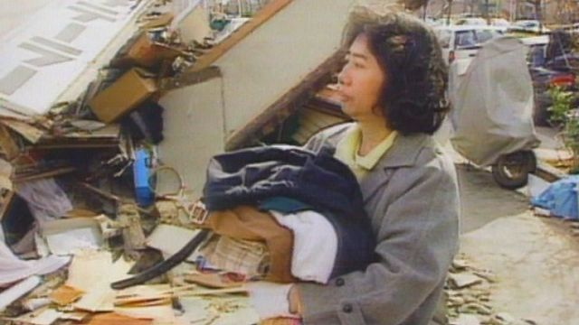 Une rescapée devant les débris de sa maison après le séisme à Kobe en 1995. [RTS]