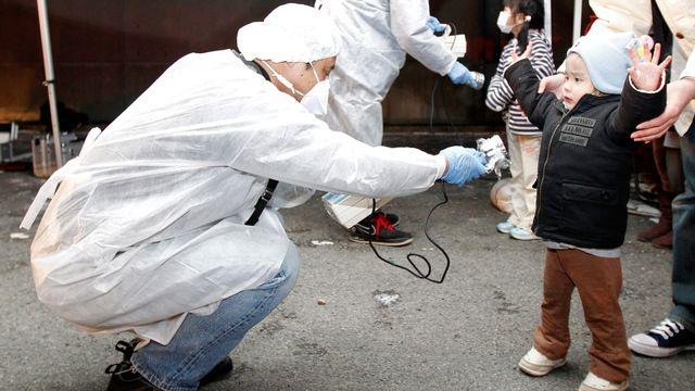 13 mars 2011, Koriyama (Japon). Un homme vérifie le taux de radiation de l'enfant qui quitte la zone d'évacuation décrétée après les accidents survenus aux centrales nucléaires de Fukushima. Cette catastrophe a été provoquée par un séisme de magnitude 9 et un tsunami, qui ont fait à eux deux près de 18'000 morts et disparus. [Kim Kyung-Hoon - Reuters]