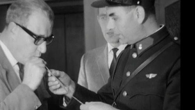 Le policier mesure le taux d'alcoolémie d'un automobiliste. [RTS]