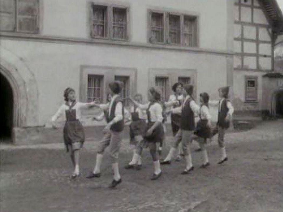 Groupe d'enfants dansant dans rue de Gruyères. [RTS]