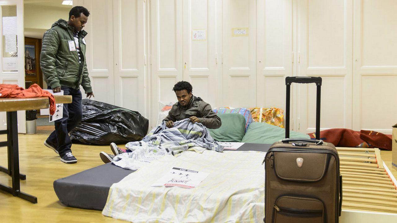 Deux des migrants installés dans l'église Saint-Laurent à Lausanne, 08.03.2015. [Jean-Christophe Bott - Keystone]